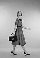 Young woman carrying suitcase