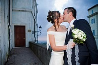 Newlyweds kissing at night