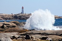 Large waves breaking on the rocks at Peggy's Cove in Nova Scotia showing the lighthouse