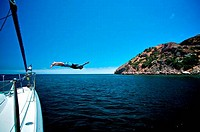 Man diving off a sailboat in the ocean, Catalina Island, California, USA