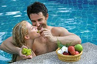 couple in love have fun in pool eating fruits