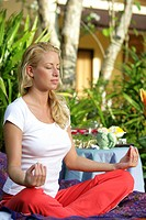 young blonde woman doing yoga on tropical garden in