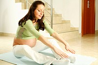 Glueckliche schwangere Frau macht Gymnastik, pregnant woman doing exercise
