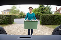 Mixed race woman putting recycling in car (thumbnail)