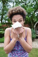 Mixed race woman blowing her nose outdoors