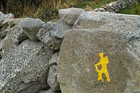 A yellow man painted on a stone wall as a waymarker on the Connemara Way, Co  Galway, Ireland