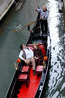 Tourist taking a gondola ride in the water canals of Venice Italy