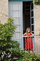 Young girl in red dress on balcony of French house