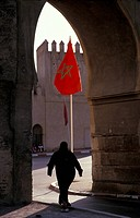 Morocco, Fes, Silhouette of man under arch in city wall, and Moroccan flag