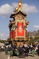 Men pulling festival float yatai through street in Gonjunko Procession during Sanno Festival of Hie Jinja Shrine, Takayama, Gifu prefecture, Japan