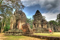 Cambodia, Angkor Wat. Female tourist with umbrella views part of Thommanon Temple. Credit: Jones_Shimlock / Jaynes Gallery / DanitaDelimont.com