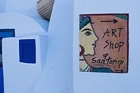 Greece, Santorini. Sign for art shop on white wall. Credit: Bill Young / Jaynes Gallery / DanitaDelimont.com