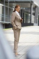 Business woman, 45 years, in front of office building