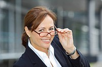 Business woman, years 45, smiling, wearing a lady's suit and looking over the top of her glasses