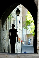 Gubbio  Umbria  Italy  A woman walks under a covered arch in the backstreets