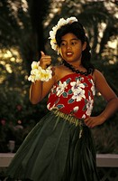 USA, Hawaii, Big Island, Girl wearing leaf skirt and flowers dances hula