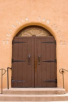 USA, New Mexico, Los Cerrillos. Front door of Saint Joseph Catholic Church. Credit: Nancy & Steve Ross / Jaynes Gallery / DanitaDelimont.com