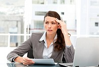 Serious female executive finding ideas while working at her desk with laptop