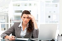 Worried businesswoman working at her desk with laptop and folder