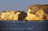 Two boats are seen in the sea while huge cliffs are seen at the back.