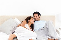 Lovely hispanic couple relaxing in their bedroom during a weekend at home