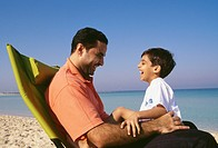 A father and son cherishing happy moments on the beach.