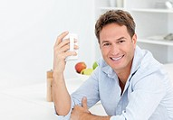 Happy man enjoying his coffee during a break in the kitchen