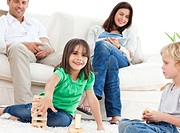 Happy children playing with dominoes in the living room with their parents