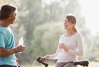 Couple on bicycles drinking water
