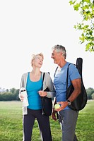 Smiling couple walking with tennis racquets
