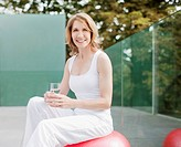 Woman sitting on exercise ball drinking water