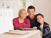 Smiling family standing near laptop