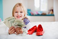 Smiling girl holding dollar bills