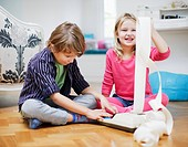 Brother and sister playing with adding machine and adding machine tape