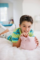 Boy laying in bed with piggy bank