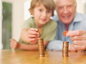 Grandfather and grandson stacking coins