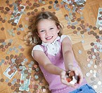 Girl laying on floor with handful of coins