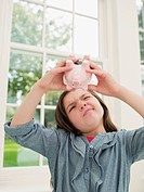 Frustrated girl emptying piggy bank
