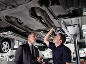 Businessman looking underneath car with mechanic (thumbnail)