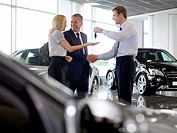 Salesman handing couple keys to new car in showroom (thumbnail)
