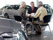Salesman talking to couple in automobile showroom (thumbnail)
