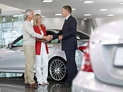 Salesman shaking hands with couple in automobile showroom (thumbnail)
