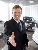 Greeting salesman in automobile showroom