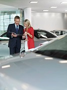 Salesman showing woman brochure in automobile showroom