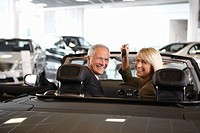 Couple holding keys to new convertible in showroom