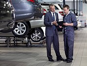 Businessman talking to mechanic in auto repair shop