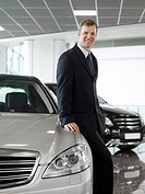 Salesman leaning on car in automobile showroom