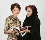 Two Arab lady reading a magazine