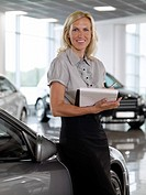 Saleswoman leaning on new car in showroom