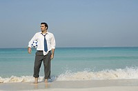 Businessman holding a football on the beach